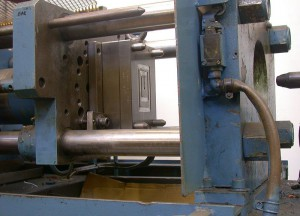 Paper clip mould opened in moulding machine; the nozzle is visible at right